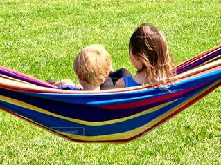 芝生の公園にあるハンモックに座る子供の写真・画像素材[4560356]