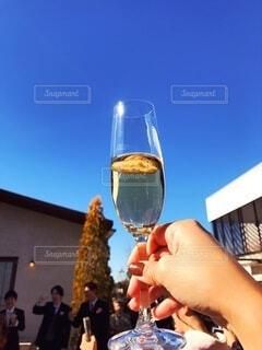 青空とワイングラスを持つ手の写真・画像素材[3847237]