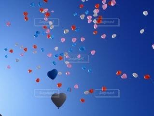 空を飛ぶカラフルなハートの風船の写真・画像素材[3847267]