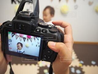 一眼レフカメラを持つ手とカメラ越しの子供の写真・画像素材[3919954]