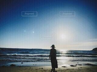 帽子をかぶって浜辺に立つ女性の写真・画像素材[3835589]