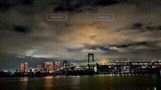 雲に反射して光る高層ビルと橋の明かり、海の写真・画像素材[3953773]