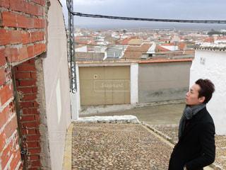 れんが造りの建物の前に立っている男の写真・画像素材[1158592]