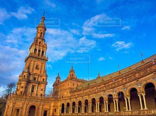 建物の側に時計と大きな背の高い塔の写真・画像素材[1721724]