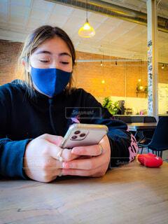 屋内で携帯電話をいじる若い女性の写真・画像素材[4751939]