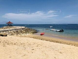 海の隣の砂浜に座っている人々のグループの写真・画像素材[3870678]