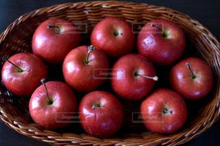 かごの上に並んだ赤いミニリンゴ達の写真・画像素材[3889657]
