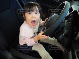 自動車の運転席に座る小さな女の子の写真・画像素材[3900586]