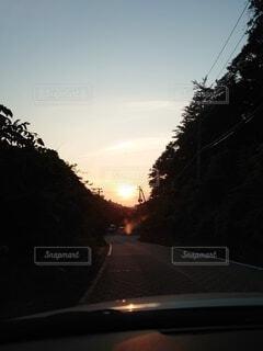 車から臨む沈んでいく夕陽の写真・画像素材[3899738]
