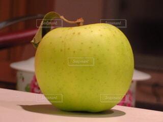 木製のテーブルの上に緑のリンゴの写真・画像素材[3912552]