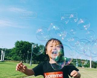 キラキラのしゃぼん玉とニコニコ笑顔の写真・画像素材[4107996]