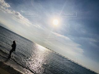 晴れた日に波に乗りながら空中を飛ぶ男の写真・画像素材[3946713]