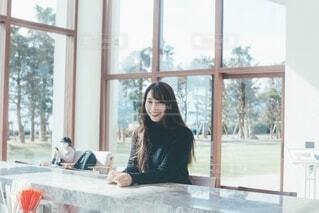 窓の前のダイニングテーブルにいる女性の写真・画像素材[4023389]