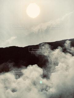 太陽と山と煙の風景の写真・画像素材[3967910]