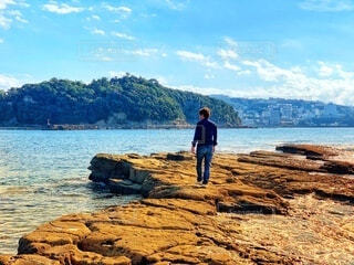 海の岩場を歩く男性の写真・画像素材[3983350]