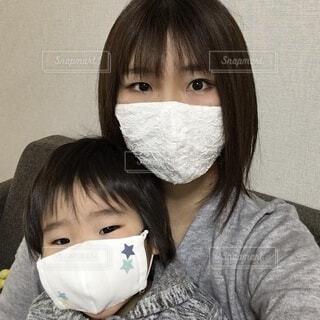 マスクをしている赤ちゃんを抱いている人の写真・画像素材[4028103]