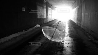 傘と奥から刺す光のある地下道の写真・画像素材[4000784]
