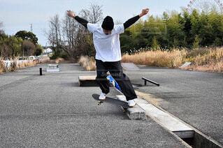 駐車場でスケートボードでいたずらをしている男の写真・画像素材[4032267]