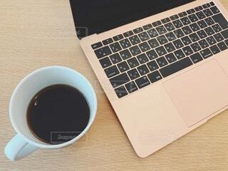 ノートパソコンとブラックコーヒーの写真・画像素材[4057429]