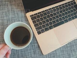 ノートパソコンとブラックコーヒーの写真・画像素材[4057430]