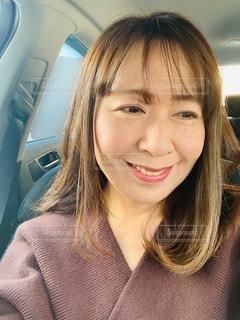 車内でテレビを観て微笑むの写真・画像素材[2988842]
