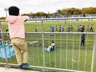 フェンスの隣に立っている人の写真・画像素材[4075480]