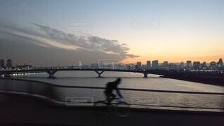 夕暮れの都市に架かる橋を抜ける自転車の写真・画像素材[4080465]