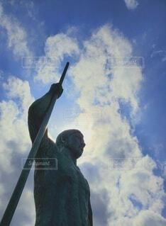 空に槍を突き立て声高に勝利を叫ぶ戦士の像に勇気が奮い立つの写真・画像素材[4398448]