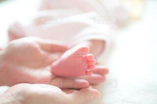 生まれたばかりの赤ちゃんの足を手のひらにそっとのせるの写真・画像素材[4087396]
