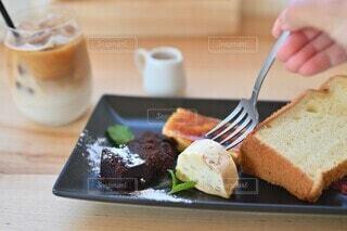 テーブルの上にケーキのお皿をおせる、食べようとする手の写真・画像素材[4597658]