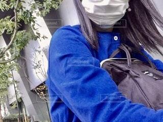 黒いバッグを抱える青い服を着た女性の写真・画像素材[4150319]