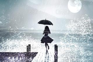 傘を持って雨の中を歩いている人々のグループの写真・画像素材[2138147]