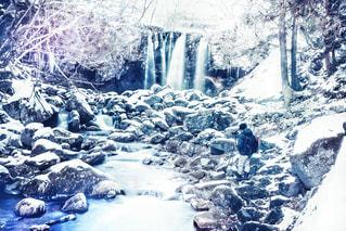 雪に覆われた斜面の側に木がある滝の写真・画像素材[2138211]
