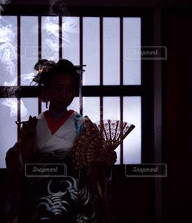窓の前に立っている人の写真・画像素材[2138256]