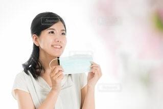 笑顔でマスクを持つ女性の写真・画像素材[4103480]