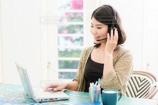 ラップトップを使ってテーブルに座っている女性の写真・画像素材[4106375]