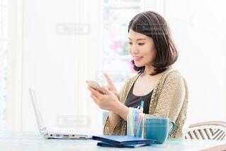 ラップトップを使ってテーブルに座っている女性の写真・画像素材[4106410]