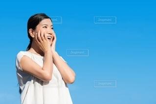 笑顔で両手を顔に添えている女性の写真・画像素材[4180322]