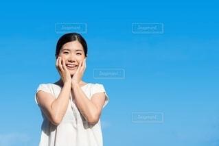 笑顔で顔に両手を添える女性の写真・画像素材[4180323]