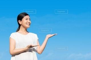 手を差し出すポーズをする笑顔の女性の写真・画像素材[4193832]