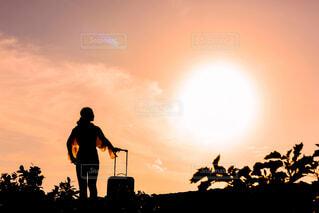 夕日の前に立つ女性の写真・画像素材[4237214]