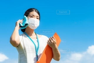 暑い夏にマスクをして汗をかきながら働く女性の写真・画像素材[4660030]