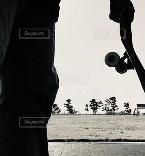 公園でスケートボードを始めようとする男の写真・画像素材[4105405]