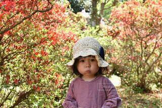 木の隣に立っている小さな男の子の写真・画像素材[4342370]