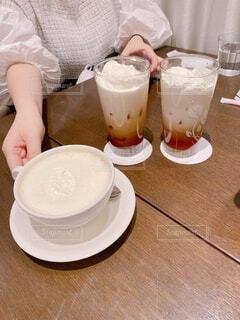 コーヒーを飲みながらテーブルに座っている人の写真・画像素材[4280034]