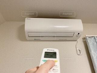 エアコンのリモコンを持つ手の写真・画像素材[4873643]