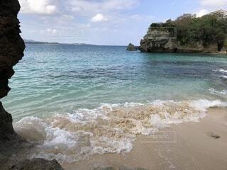 水の体の隣の岩場の海岸にある人々のグループの写真・画像素材[4170779]