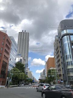 高層ビルの隣の通りを走る車の写真・画像素材[4175768]