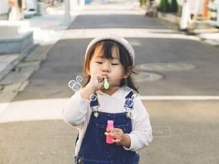 家の前でシャボン玉を吹く女の子の写真・画像素材[4149452]