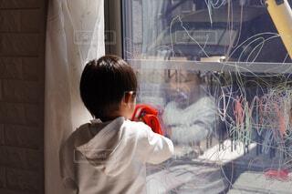 窓に描いたクレヨンの落書きを掃除しているところの写真・画像素材[4263307]